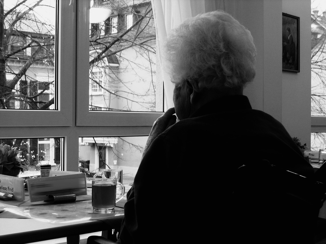 Lonely older woman looking out a window